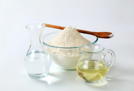 sunflower oil: white wheat flour in a glass bowl with a wooden spoon, a carafe of cold water and a jug of sunflower oil