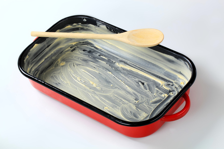 greased: red baking pan greased with butter Stock Photo