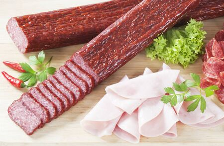 air dried salami: sliced salami and ham on wooden cutting board