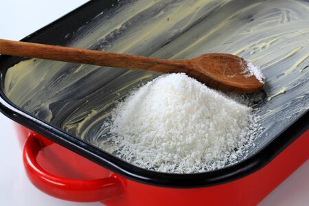 greased: heap of desiccated coconut in greased baking pan