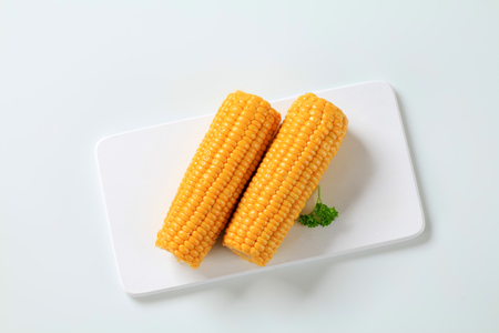 accompaniment: two boiled corn cobs on white cutting board