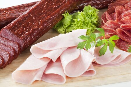 air dried salami: variety of salamis on the wooden cutting board