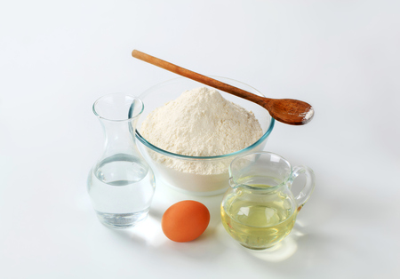 sunflower oil: wheat flour,  carafe of cold water, jug of sunflower oil and an egg