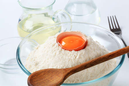 cooking oil: bowl of flour with yolk, carafe of water and jug of cooking oil