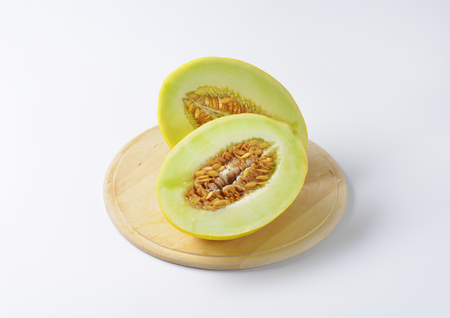 halved  half: Two yellow melon halves on cutting board Stock Photo