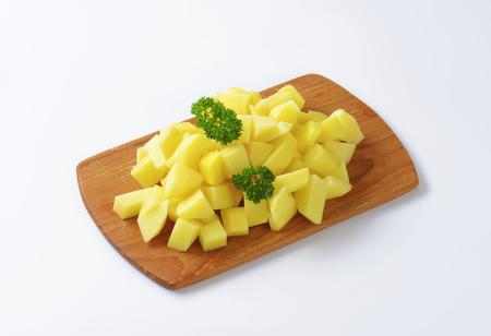 diced: Heap of raw diced potatoes on cutting board