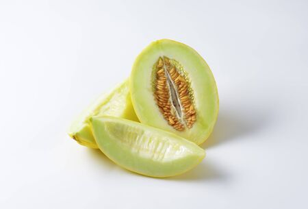 halved  half: Yellow melon half and slices on white background Stock Photo