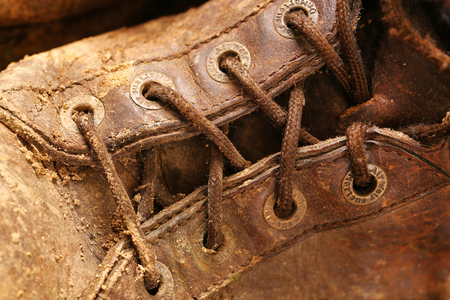 muddy clothes: Brown leather boot covered with mud