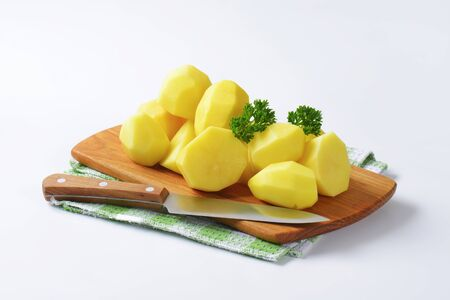 halved  half: Heap of fresh peeled potatoes on cutting board Stock Photo