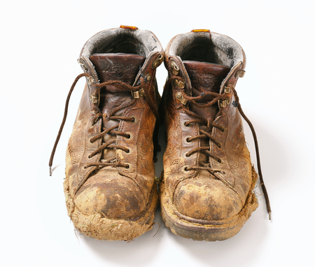 muddy clothes: Pair of dirty brown walking boots