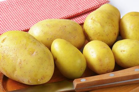unpeeled: Unpeeled new potatoes on cutting board Stock Photo