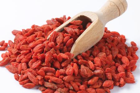 lycium: Pile of dried goji berries and wooden scoop