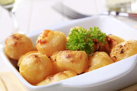 prepared potato: Cheese coated potatoes in square ceramic dish Stock Photo