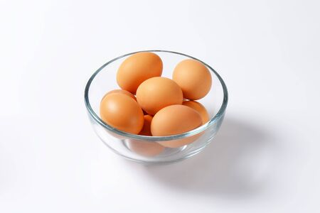 glass bowl: Brown organic eggs in a glass bowl