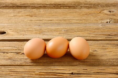brown eggs: Three brown eggs on wooden surface