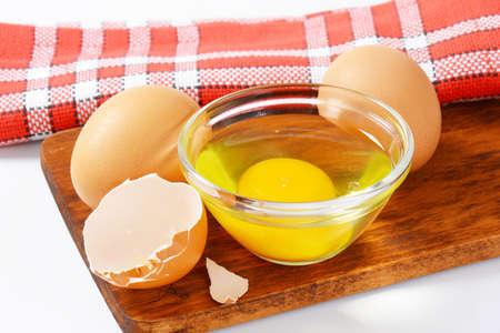 huevo blanco: Fresh egg white and yolk in glass bowl, two whole eggs and eggshell