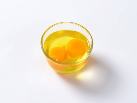 Fresh egg whites and yolks in glass bowl