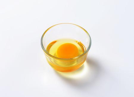 huevo blanco: clara de huevo fresco y yema de huevo en un taz�n de vidrio Foto de archivo