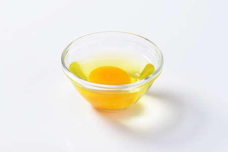 huevo blanco: clara de huevo fresco y yema de huevo en un tazón de vidrio Foto de archivo