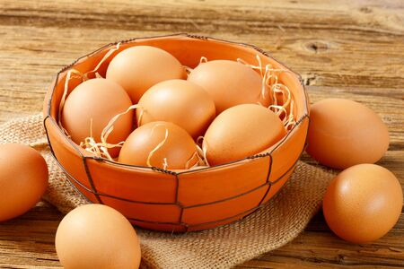 brown eggs: Fresh brown eggs in terracotta bowl and next to it on wooden table Stock Photo