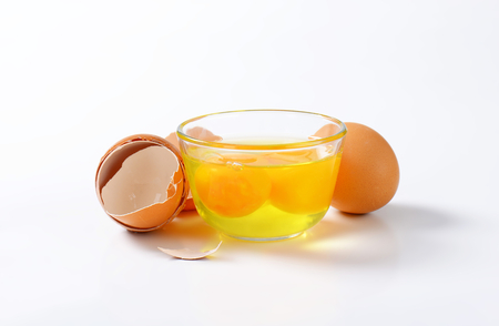 Fresh egg whites and yolks in glass bowl, one whole egg and empty eggshells Stock Photo