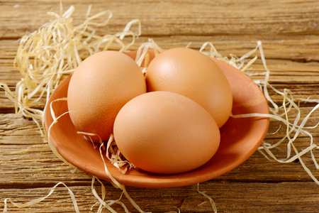 brown eggs: Three brown eggs on terracotta plate on wooden background Stock Photo