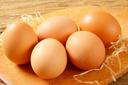 brown eggs: Brown eggs on cutting board on wooden surface Stock Photo