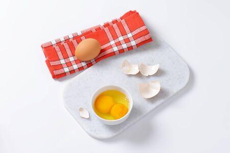 yolks: Fresh egg whites and yolks in white bowl Stock Photo