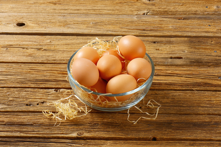 brown eggs: Brown eggs in a glass bowl  on wooden background