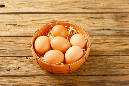 brown eggs: Fresh brown eggs in terracotta bowl on wooden table