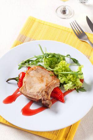 salad greens: Roast pork chop and red pepper garnished with salad greens