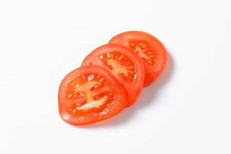 tomato slices: Red tomato slices on white background