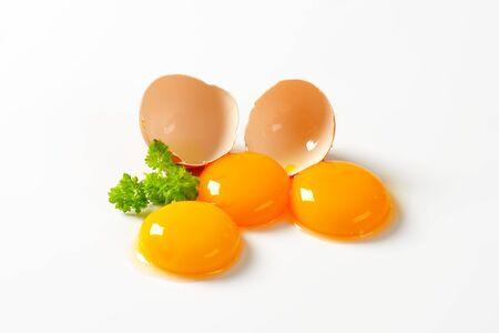 eggshell: Three fresh egg yolks and empty eggshell Stock Photo