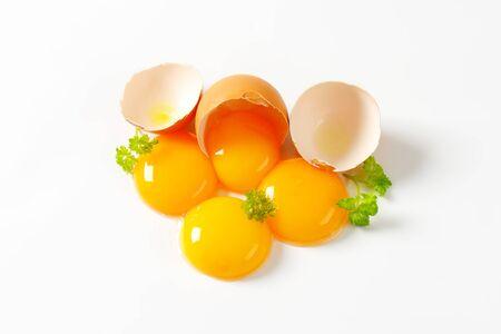 yolks: Four fresh egg yolks and eggshell Stock Photo