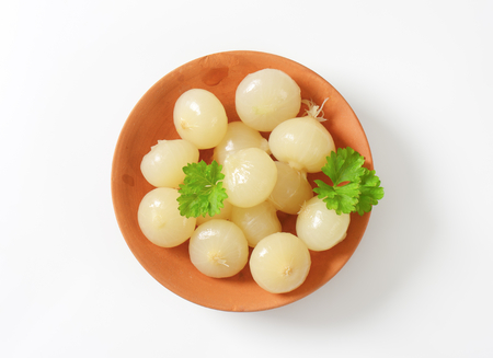 accompaniment: Small pickled onions on terracotta plate Stock Photo
