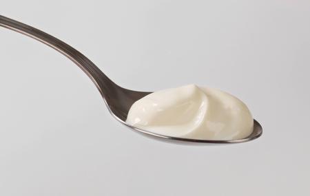 spoonful: Spoonful of smooth plain yogurt Stock Photo
