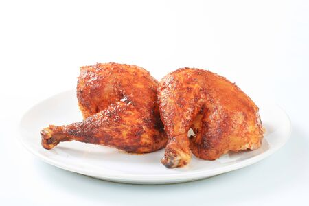 quarters: Two garlic roasted chicken leg quarters on plate Stock Photo