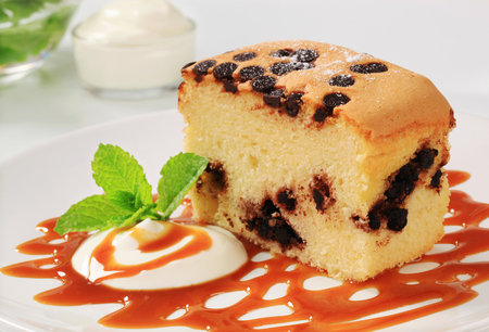 caramel sauce: Piece of sponge cake with chocolate chips, cream and caramel sauce on a white plate