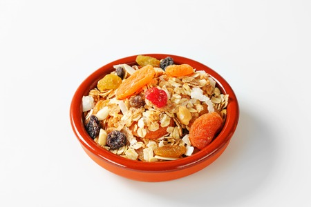 Bowl of rolled oats with various dried fruit pieces and nuts Stock Photo