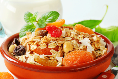 avena en hojuelas: Bowl of rolled oats with various dried fruit pieces and nuts Foto de archivo