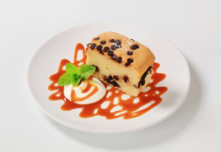 caramel sauce: Piece of sponge cake with chocolate chips, cream and caramel sauce Stock Photo