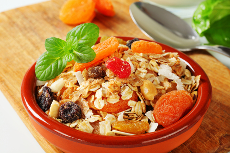 rolled oats: Bowl of rolled oats with various dried fruit pieces and nuts Stock Photo