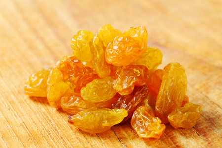 sultanas: heap of golden-coloured raisins (sultanas) on a wooden background