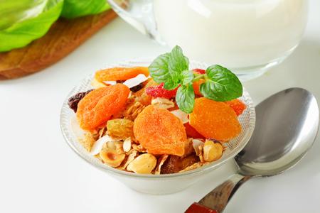 avena en hojuelas: Tazón de copos de avena con varias piezas de fruta seca y nueces