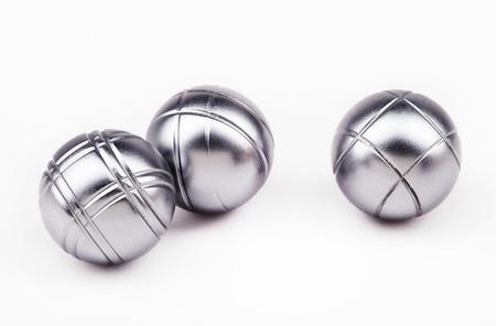 tři těžké petanque koule na bílém pozadí