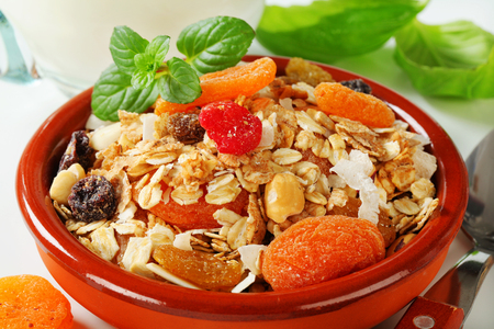 rolled oats: Bowl of rolled oats with various dried fruit pieces and nuts Foto de archivo