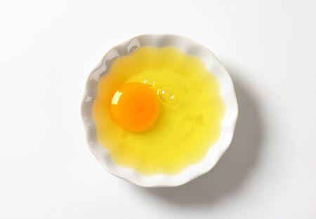 Fresh egg white and yolk in a bowl