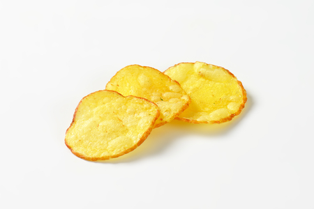 nibbles: Three potato chips on white background