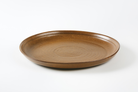 Round brown earthenware dinner plate Stock Photo