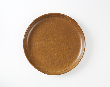 earthenware: Round brown earthenware dinner plate Stock Photo